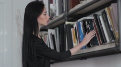 Woman takes a book from the shelf and opened. Stock Footage