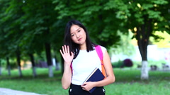 Woman waves hand and smiles to camera and touches hair on a green background. Stock Footage