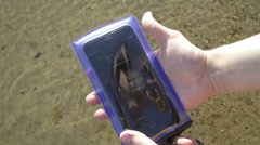 Smartphone in a waterproof pouch lay down in the water Stock Footage