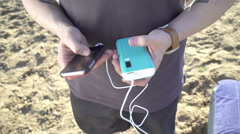The young man with gadget to charge your smartphone - stock footage