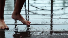 Young girl dancing barefeet under the rain enjoying warm summer weather - stock footage