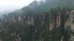 CINEMATIC AERIAL FLY OVER ZHANGJIAJIE STEEP ROCK CLIFFS TO TOURISTS WAVING BELOW Stock Footage