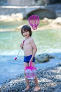 Cute boy with fishing net and bucket, trying to catch some little fishes in t Stock Photos