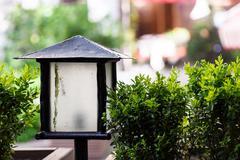 A street lantern close up at a summer cafe terrace with green shrubs Stock Photos