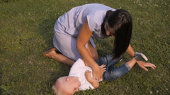 Mother And her Son Having Fun On Grass In Park. Mom Tickling And Kissing Son Stock Footage