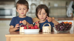 Two sweet children, boy brothers, eating fresh fruits at home, strawberries,  Stock Footage