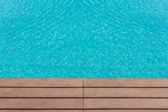 Edge of artificial wood floor near swimming pool Stock Photos