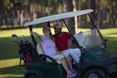 couple in buggy on golf course - stock photo