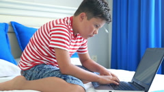 Child lying on a bed and using laptop computer 3 Stock Footage