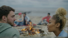 4K Happy relaxed friends sitting around a bonfire on the beach Arkistovideo