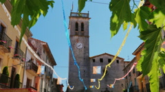 Clock tower on an old church in a small Spanish town. Hang flags of Catalonia Stock Footage