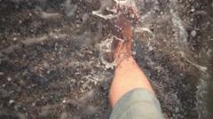 Male feet walking along sandy beach Stock Footage