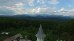 Christian church on top of green hill with mountain range, aerial view Stock Footage