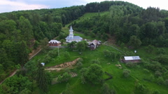 Christian church on top of green hill surrounded by forest, camera flight Stock Footage