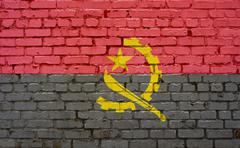 Flag of Angola painted on brick wall, background texture Stock Photos