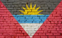 Flag of Antigua Barbuda painted on brick wall, background texture Stock Photos