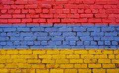 Flag of Armenia painted on brick wall, background texture Stock Photos