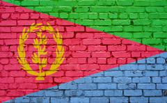 Flag of Eritrea painted on brick wall, background texture Stock Photos