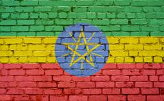 Flag of Ethiopia painted on brick wall, background texture Stock Photos