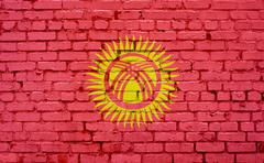 Flag of Kyrgyzstan painted on brick wall, background texture Stock Photos
