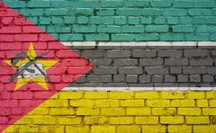 Flag of Mozambique painted on brick wall, background texture Stock Photos