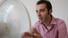 A flushed man in front of a fan Stock Footage