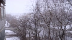 On snow-covered the street during a snowfall in slowmotion. Changes focus to Stock Footage