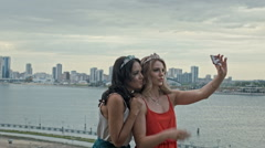 Two young beautiful girls having fun and making selfie on high hill over the Stock Footage