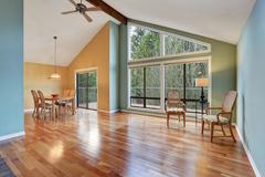 Empty room with dining area with hardwood floor and big windows - stock photo