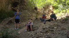 Mom and 3 children rest in shade along mountain trail Stock Footage