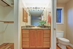 Simple bathroom interior with vanity cabinet and granite counter top, hardwoo Stock Photos