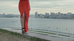 Feet of young woman in a red dress walking in the wind with fluttering dress Stock Footage