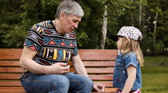 Grandfather spending time with her granddaughter on a park bench - stock footage