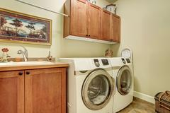 Laundry room with modern appliances, brown vanity cabinet with drawers. - stock photo