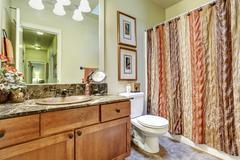 Modern bathroom interior with vanity cabinet, tile floor and dark granite cou - stock photo