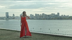Attractive girl in a red dress stands over the citi in the wind with fluttering Stock Footage