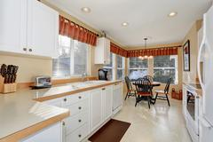 White kitchen cabinets with steel appliances and light tone tile floor. Conne Stock Photos