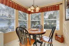 Cozy dining area with table set and windows around Stock Photos