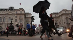 Tourists walk in Piccadilly Circus with Eros Statue in background - stock footage