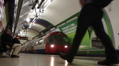 Passengers watch tube train arrive at Piccadilly Circus Underground Staion Stock Footage