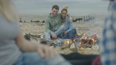 4K Happy friends sitting around a bonfire on the beach, young couple talking Stock Footage