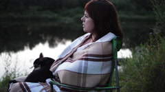 Women Sitting on the Bank of the River. on Lap Dog Lying Stock Footage