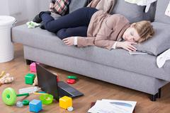 Exhausted after whole day of motherly and office duties Stock Photos