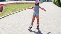 Back of girl in pink helmet riding on roller skates in summer park Stock Footage
