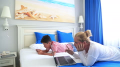 Mother and son lying on a bed and using digital equipment 5 Stock Footage