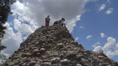 Three children climb down from conglomerate peak. Stock Footage