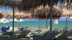 Empty sunbeds with parasols at the beach. Stock Footage