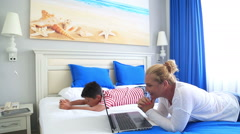 Mother and son lying on a bed and using digital equipment 6 Stock Footage