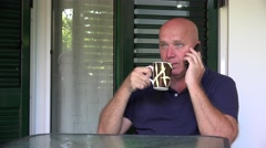 Serious man dial phone number talk business and drink a cup of coffee. Stock Footage