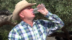 Thirsty farmer olive tree orchard owner drinking water in a hot day. Stock Footage